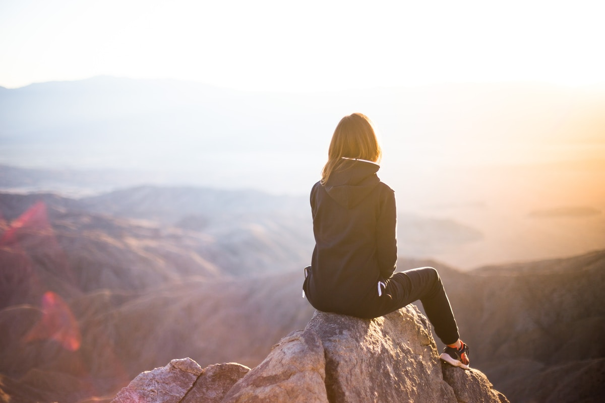 person sitting on top of gray rock overlooking mountain during daytime